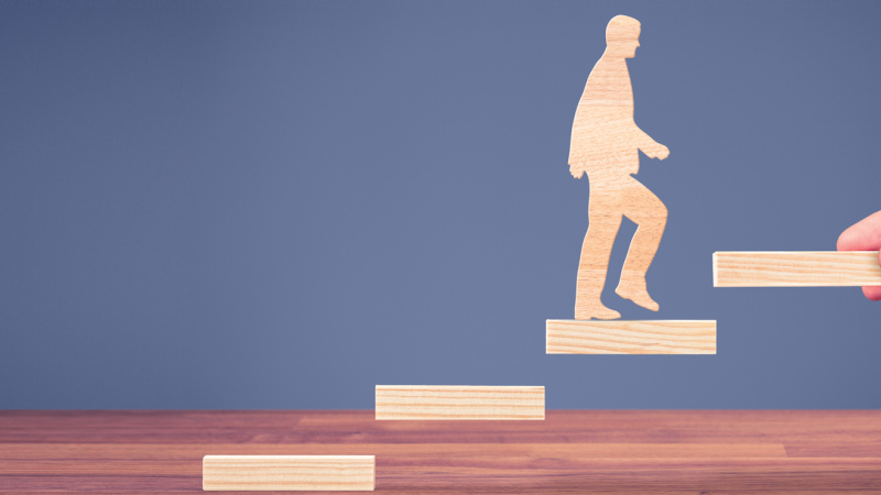 wooden cut-outs of man and stair with last step held by human hand